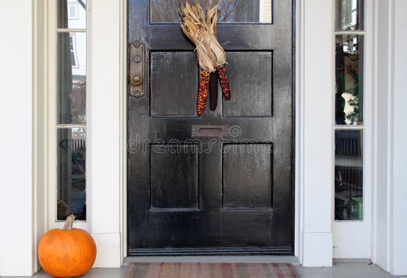 黑色门用印第安玉米和秋天南瓜 图库摄影