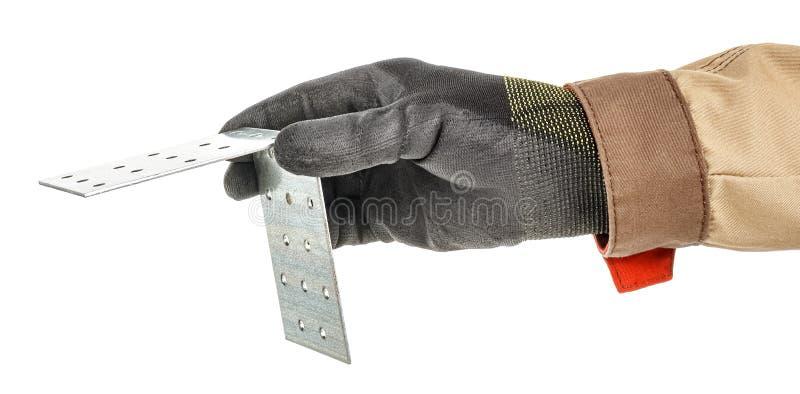 黑色防护手套和棕色制服中的工人手握有镀锌金属安装支架,该支架上有白色隔离孔 库存图片