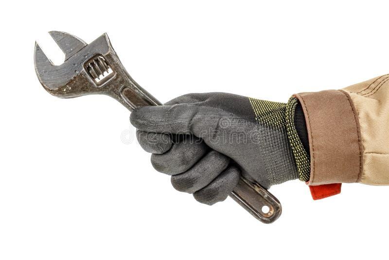 黑色防护手套和棕色制服中的工人手握着白色背景上突显的大型可调扳手 免版税库存图片