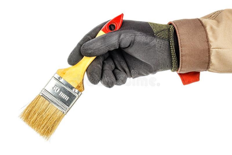 黑色防护手套和棕色制服中的男子手保持白色背景上隔离的未使用的建筑画笔 免版税库存照片