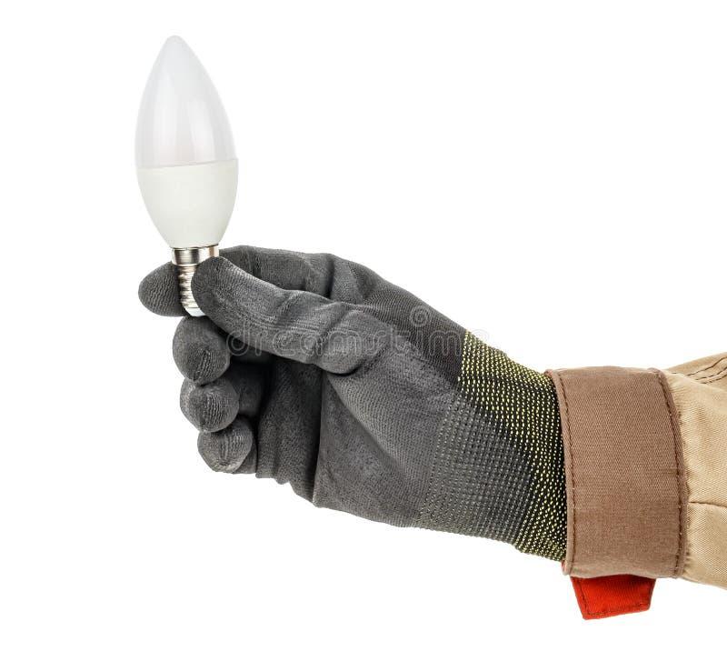 黑色防护手套电工手烛形LED灯泡及白色背景上突显的棕色均匀 库存照片