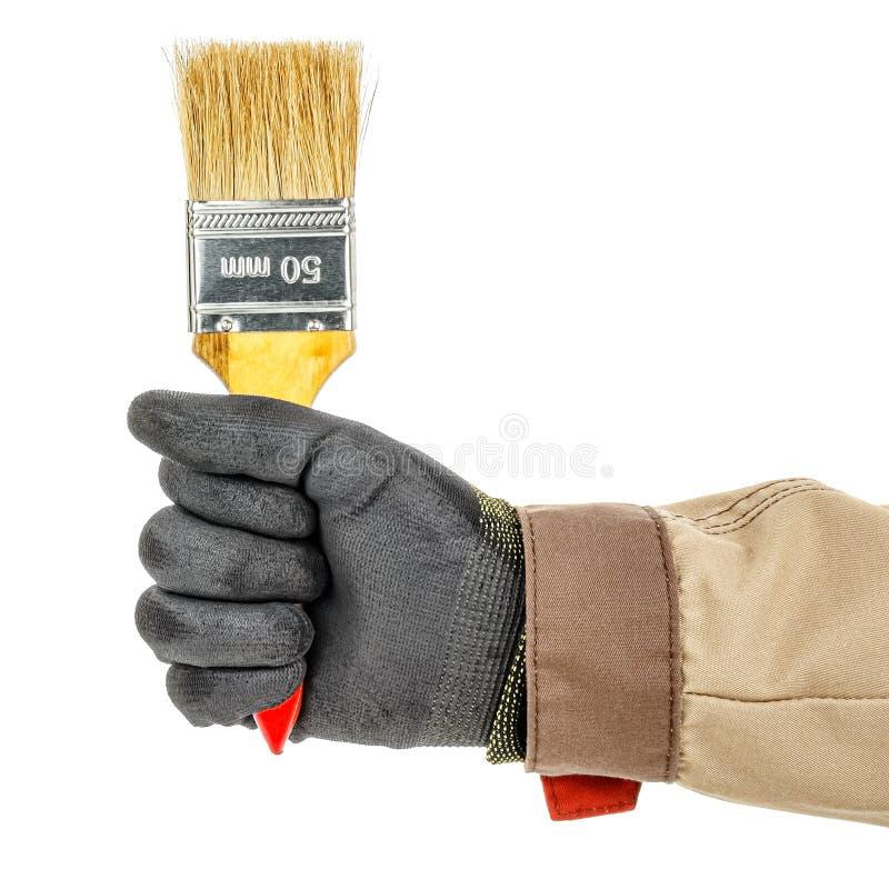 黑色防护手套的工人手与白色背景上孤立的未使用建筑画笔的棕色制服 库存照片