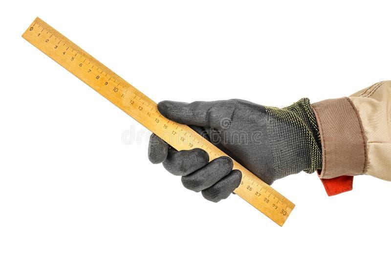 黑色防护手套的木匠手和棕色制服保持白色背景中突显的公尺木尺 库存图片