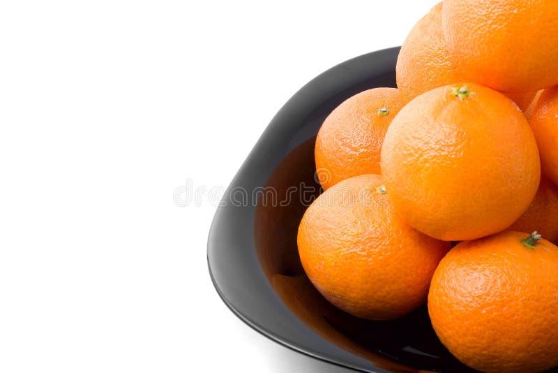 黑色鲜美查出的橙色牌照的tangerins 免版税库存照片