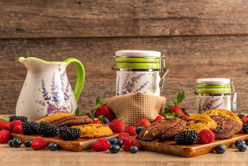 黑莓、蓝莓、莓、曲奇饼和白色陶瓷船 免版税库存照片