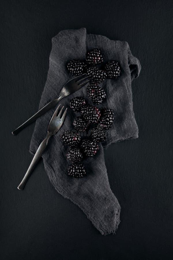 黑莓的单色食物图片在餐巾的和板岩镀厨房用桌 库存照片