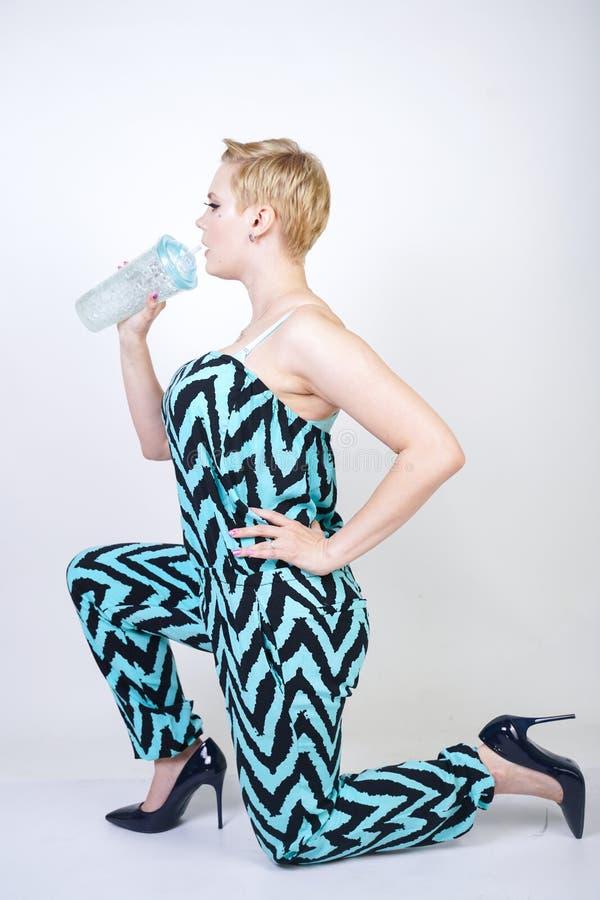 黑蓝色连衫裤的迷人的正大小年轻女人有杯的在白色背景的水在演播室 俏丽的白肤金发的女孩wearin 免版税库存图片