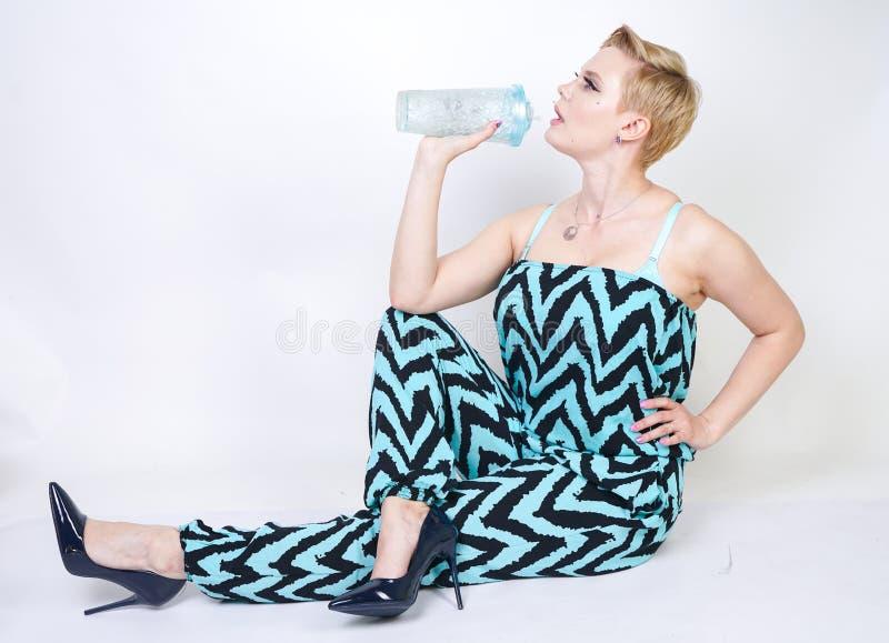 黑蓝色连衫裤的迷人的正大小年轻女人有杯的在白色背景的水在演播室 俏丽的白肤金发的女孩wearin 免版税库存照片