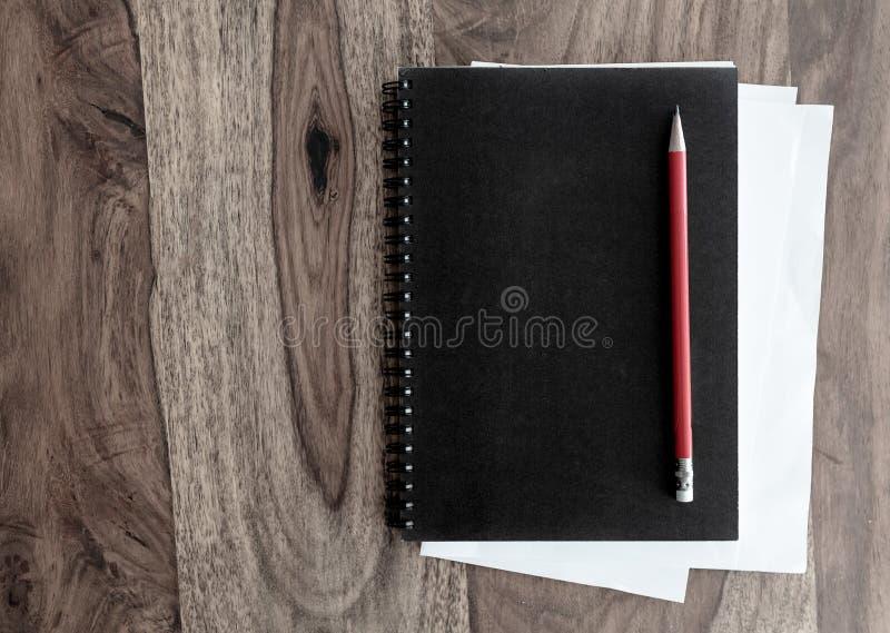 黑螺纹笔记本和笔在木桌上 库存图片