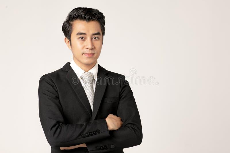 黑衣服常设十字架的年轻亚裔商人他的在白色背景的胳膊 工作室接近的射击 免版税库存照片