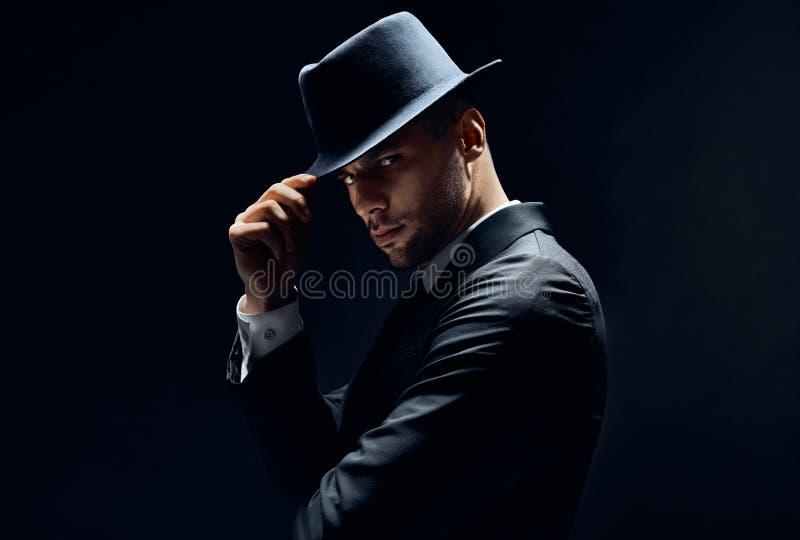 黑衣服的年轻帅哥接触他的在黑暗的背景的帽子 库存照片