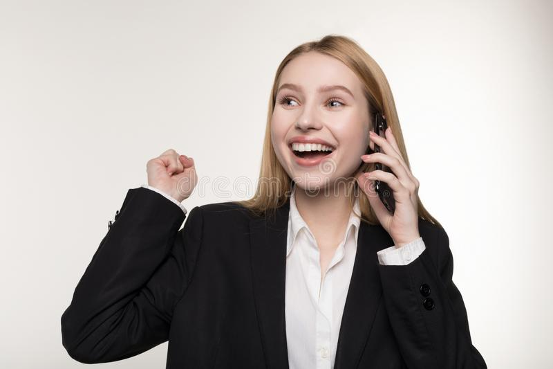 黑衣服的美丽的白肤金发的企业夫人在手机和微笑谈话 免版税库存照片