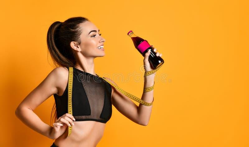 黑衣服神色的逗人喜爱的年轻健身女孩到照相机里和保持手头测量的磁带和的瓶 库存照片