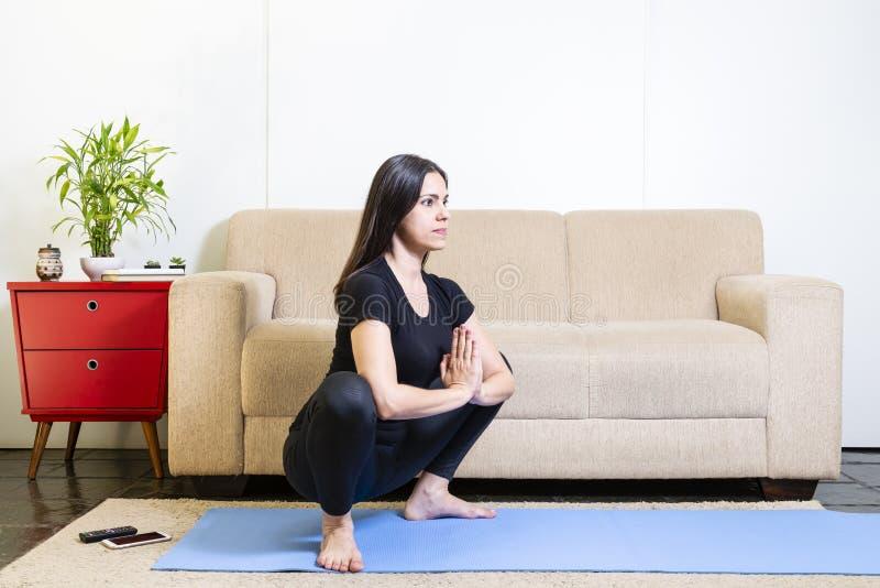 黑衣裳的美丽的白种人深色的妇女在蓝色瑜伽 库存图片