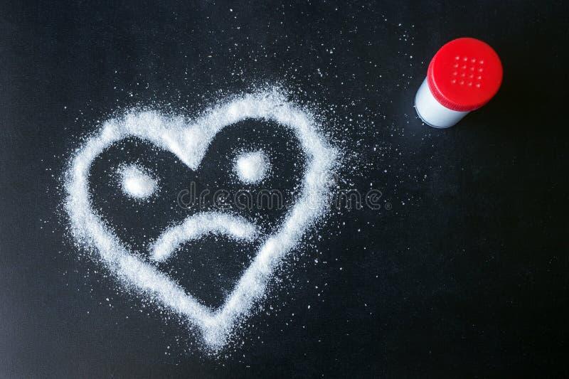 黑表面上驱散的盐 与一张哀伤的面孔的拉长的心脏 图库摄影