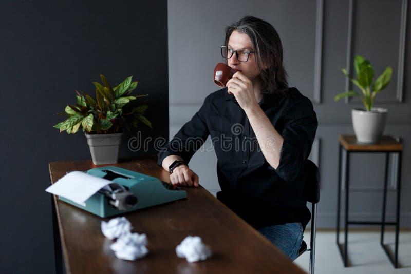 黑衬衣和眼睛玻璃的年轻人,喝在运转的书桌上的咖啡工作想法的,在灰色内部 库存照片