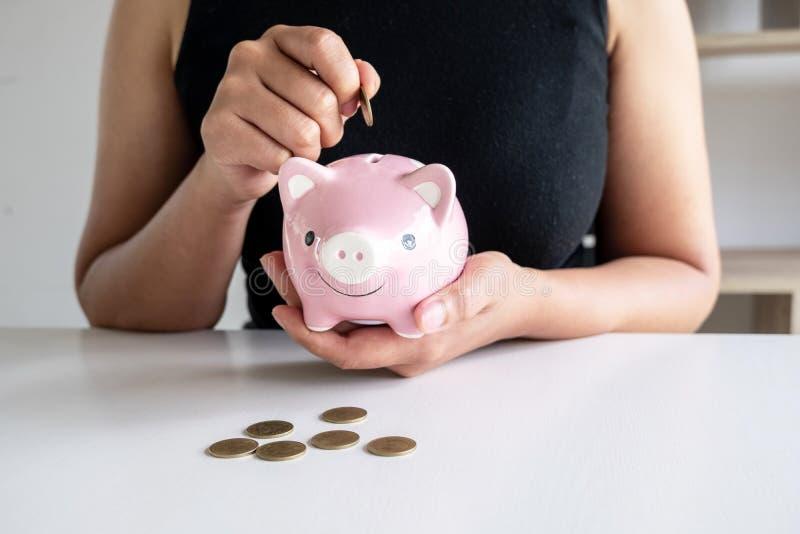 黑衬衣的妇女教成套工具对投入硬币在桃红色存钱罐中 免版税库存照片