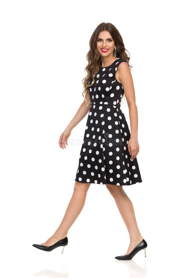 黑被加点的燕尾服和高跟鞋的微笑的美丽的年轻女人在照相机的走和Lokking 库存图片