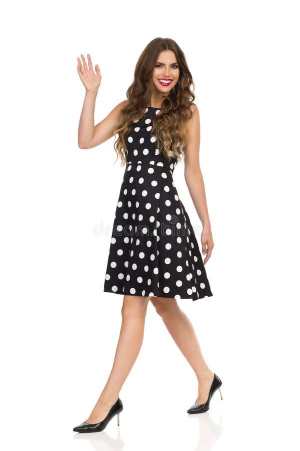 黑被加点的燕尾服和高跟鞋的美丽的年轻女人是走和摇手 免版税库存图片