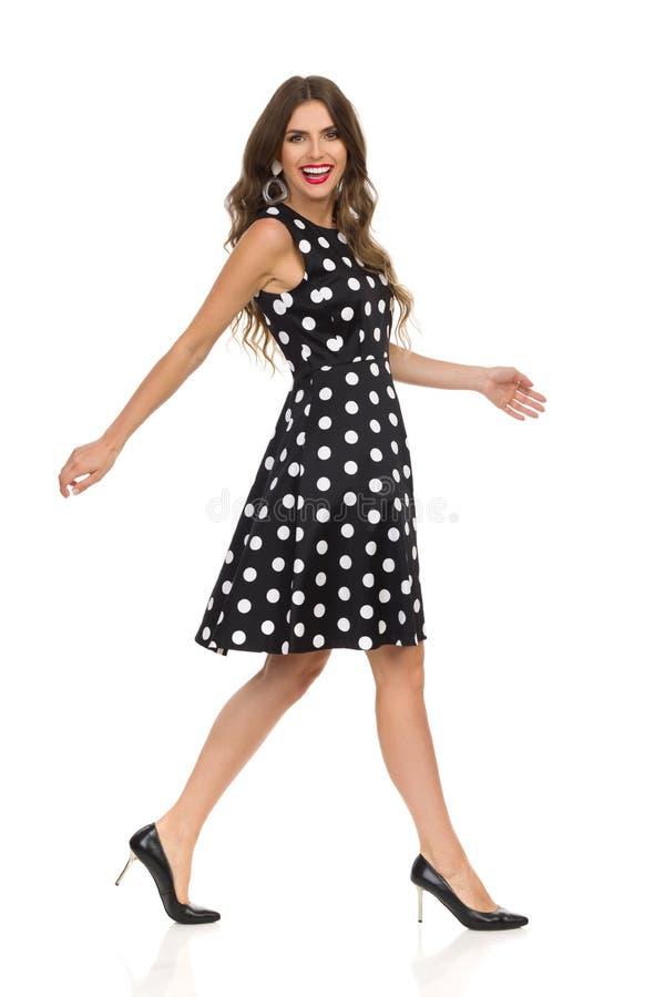 黑被加点的燕尾服和高跟鞋的美丽的年轻女人走并且笑 免版税图库摄影
