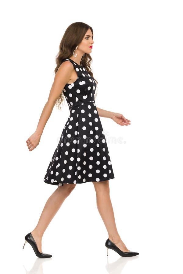 黑被加点的燕尾服和高跟鞋的美丽的年轻女人走 库存图片