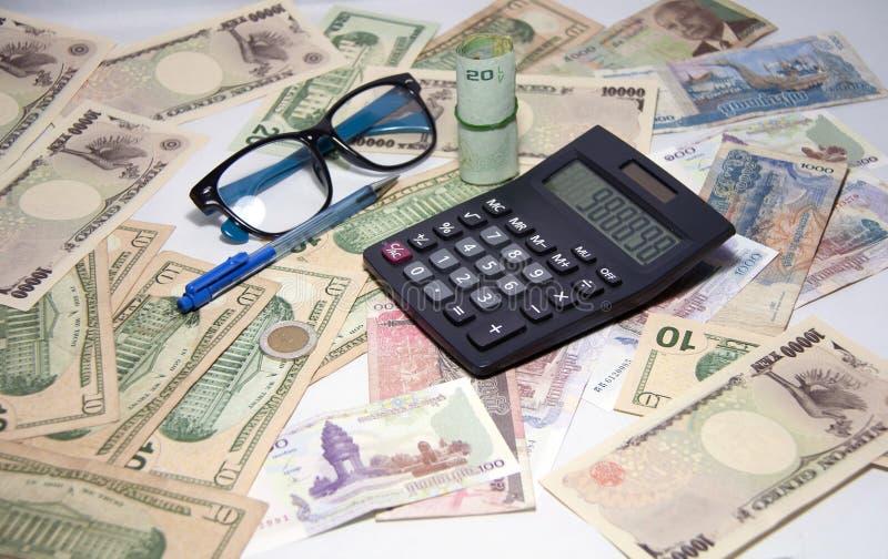 黑计算器和蓝色圆珠笔和眼镜与卷泰国钞票使用一个橡皮筋儿在各种各样的国家钞票 免版税库存图片