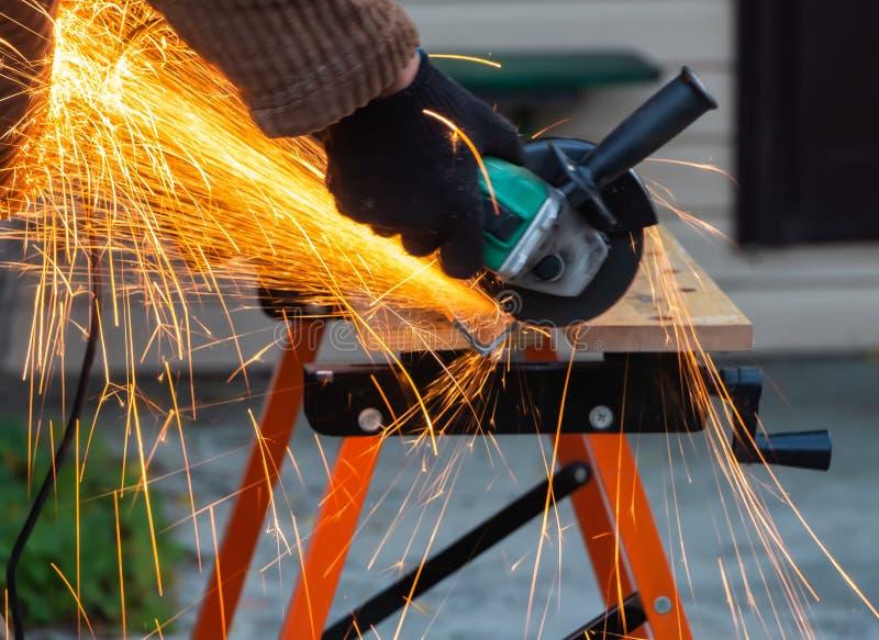 黑运作的手套的一个人切开金属使用有美丽的黄色火花的一个角度研磨机工具在工作台 免版税图库摄影