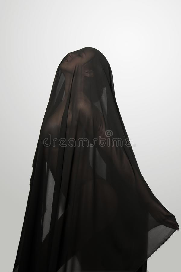 黑透明面纱的女孩在面孔 概念性画象在演播室 库存图片