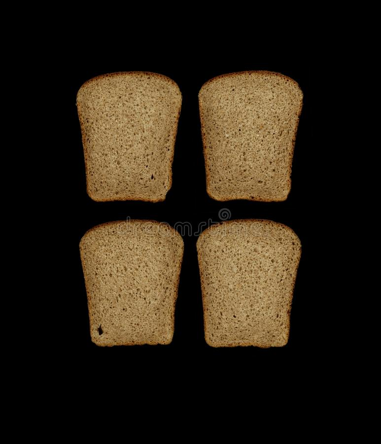 黑酵母黑麦面包四个片断从在黑背景隔绝的大面包切除了 免版税库存图片
