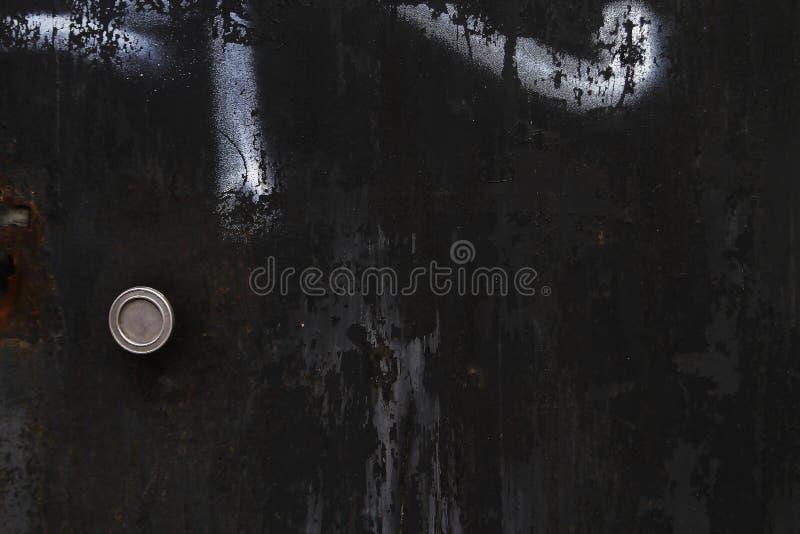 黑金属车库门 葡萄酒与街道画的门纹理 免版税图库摄影