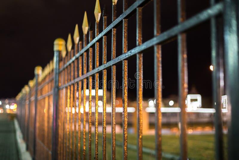 黑铁伪造的篱芭在与选择聚焦的晚上和boke迷离和反射 免版税库存图片