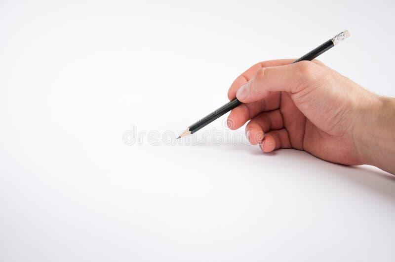 黑铅笔在他的右手举行 ? 免版税库存照片
