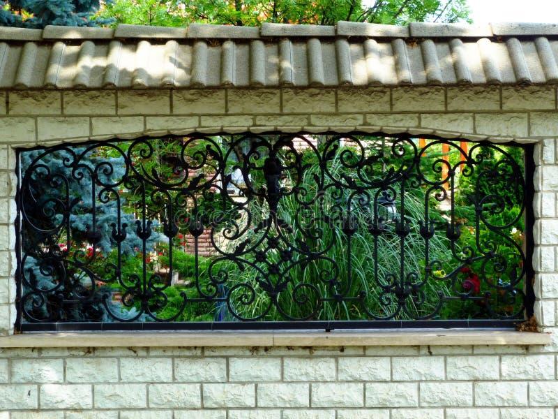 黑锻铁篱芭在白色混凝土墙和豪华的绿色庭院 免版税库存图片