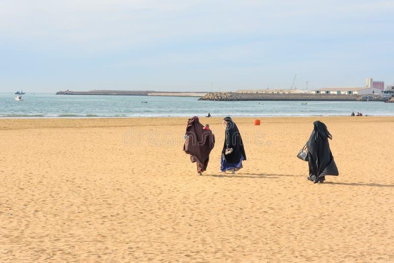 黑长的褂子的回教妇女走在海滩的 阿加迪尔 摩洛哥 免版税图库摄影
