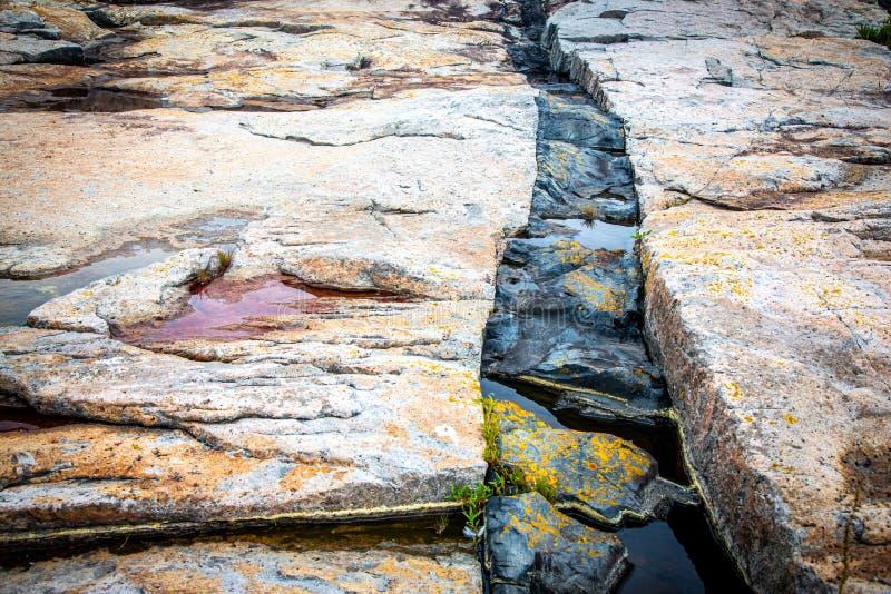 黑闯入火玄武岩堤堰岩石和花岗岩在Schoodic点在阿科底亚国家公园,缅因,美国 库存照片