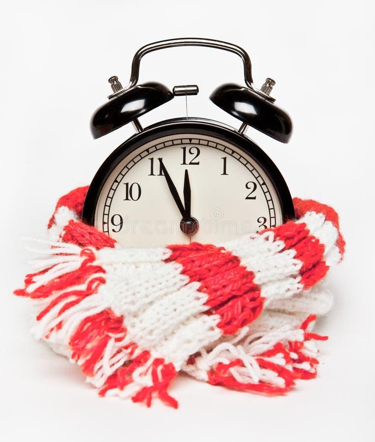 黑闹钟在一条温暖的被编织的红色和白色围巾被包裹 时间,大约十二 免版税图库摄影