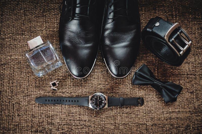 黑鞋子、黑腰带级选手、黑手表、黑蝴蝶、链扣和香水在棕色背景与袋装 免版税图库摄影