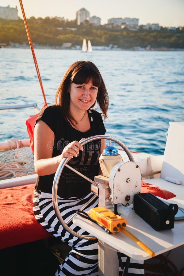 黑驾驶豪华帆船的衬衣和镶边的裙子的年轻俏丽的微笑的妇女在海,日落 免版税库存图片