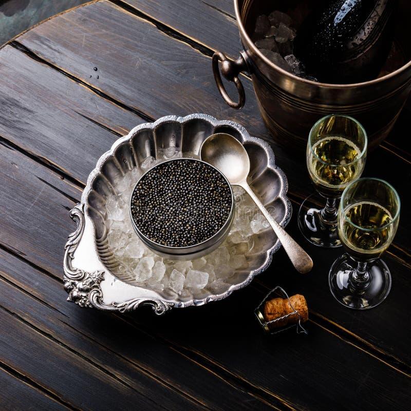 黑鱼子酱在银色碗和香槟的冰能 库存照片