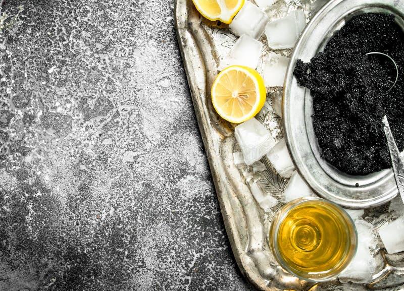 黑鱼子酱用白葡萄酒和切片柠檬 免版税库存图片