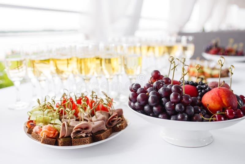 黑麦面包三明治,点心,在白色板材的bruschetta 庄严的宴会 全部在桌上的玻璃香槟或酒 免版税库存图片