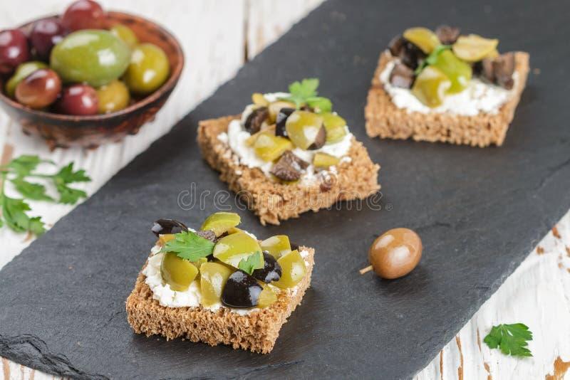 黑麦面包多士点心用卡拉迈,黑和绿橄榄,希脂乳chees 免版税库存照片