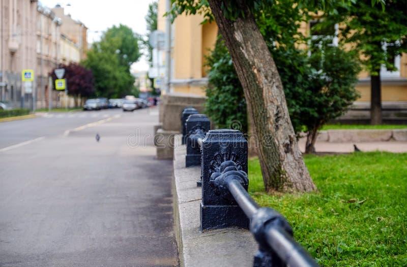 黑,伪造,在低砂岩墙壁上的金属栏杆后退入距离 草和树能通过栏杆被看见 库存照片