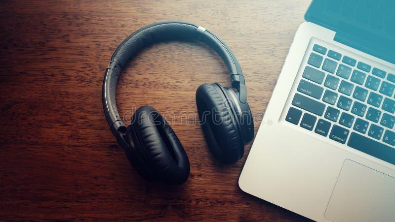 黑bluetooth耳机顶视图有手提电脑的 库存图片