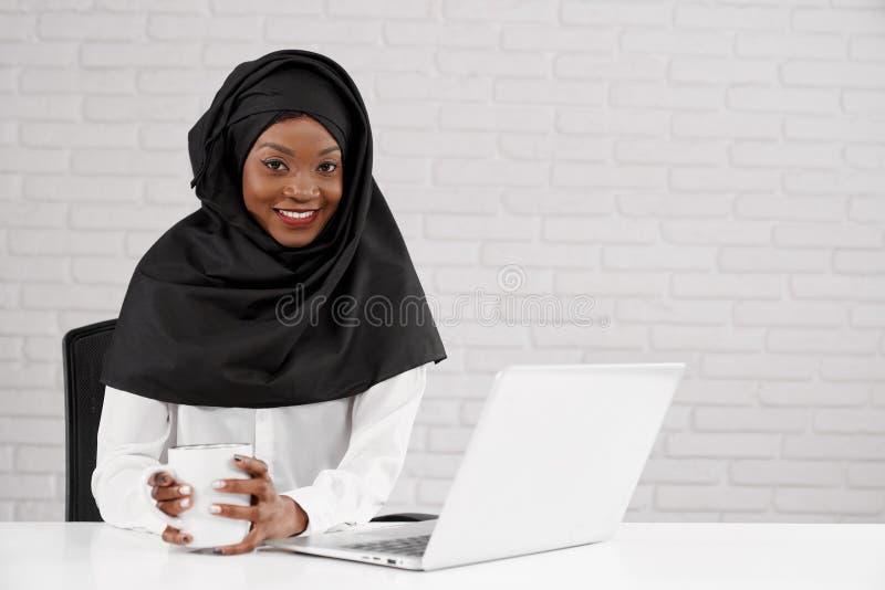 黑hijab摆在的非洲女性办公室工作者 库存照片