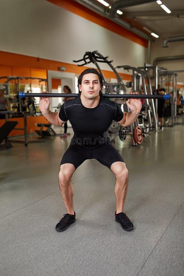 黑sportwear的年轻运动的人与做在健身房的杠铃蹲坐 免版税库存图片
