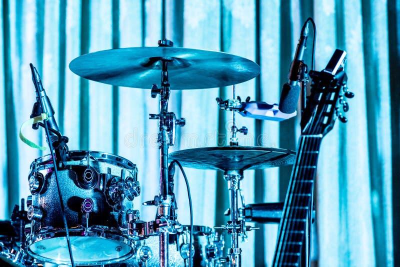 鼓在与吉他和铙钹的蓝色光设置了 免版税库存照片