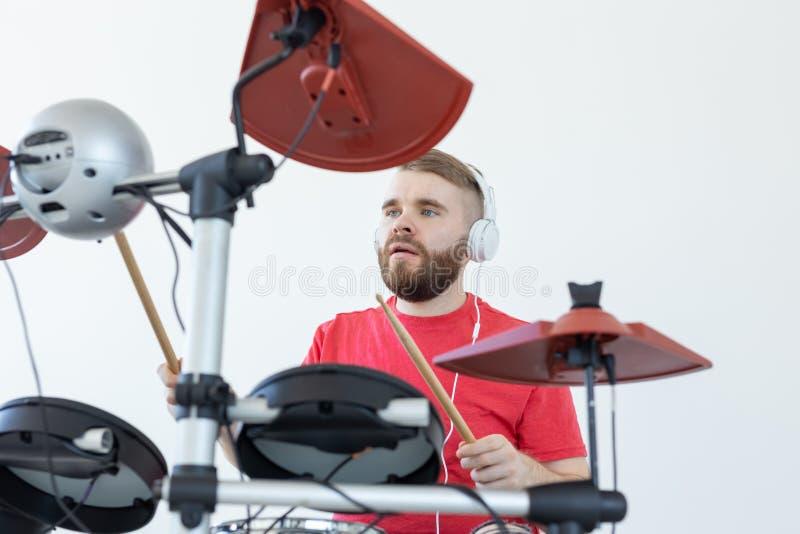 鼓手、爱好和音乐概念-播放电子鼓的红色衬衣的年轻人鼓手 免版税库存照片