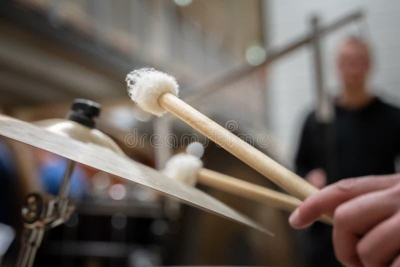 鼓手被击中的铙钹的模糊的特写镜头用鼓棍子 在铙钹的焦点 免版税图库摄影
