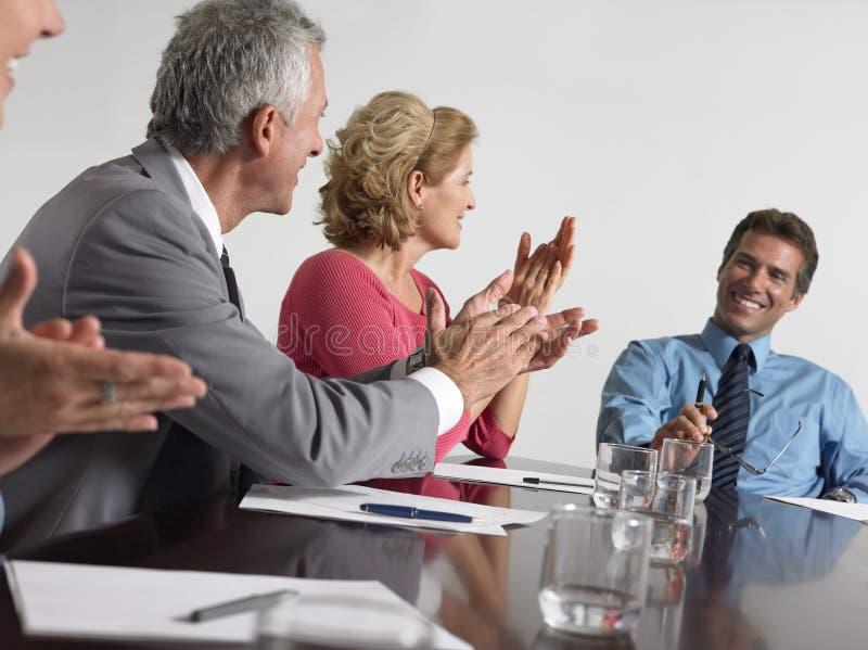 鼓掌在会议室的商人 免版税库存图片